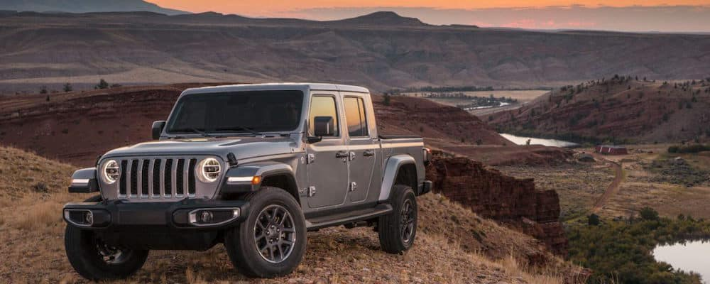 Gray Jeep Gladiator parked in mountains overlooking a valley with a stream