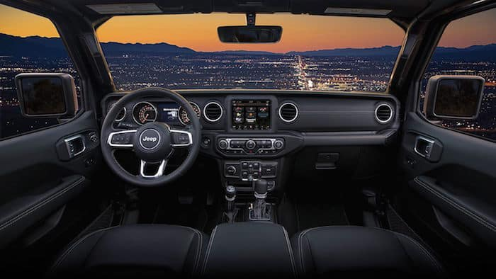 Front-seat view of 2019 Jeep Wrangler Sahara interior at dusk