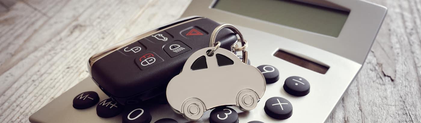 Car keys resting on top of a calculator