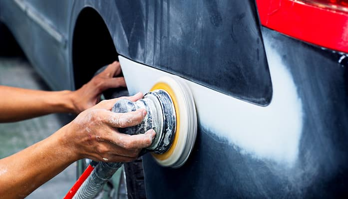 Mechanic performing auto body repair on rear of navy blue car