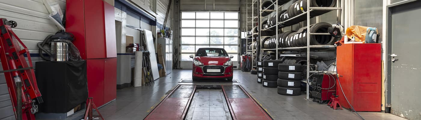 Red car parked inside auto repair shop with lift