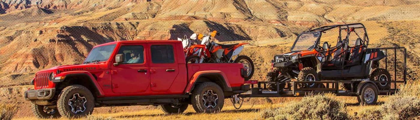 Red Jeep Gladiator towing an ATV in the desert