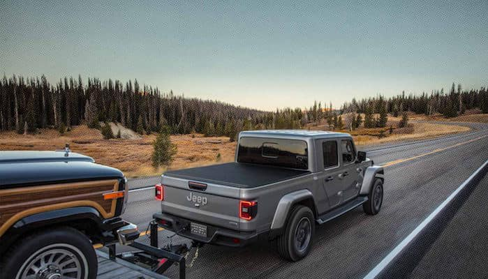 Gray jeep Gladiator towing another car on the highway