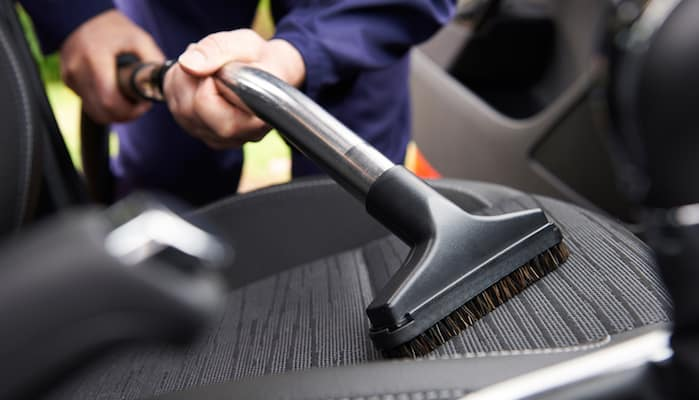Mechanic vacuuming car seat