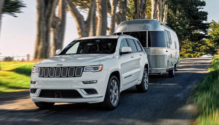 White Jeep Grand Cherokee towing an airstream trailer
