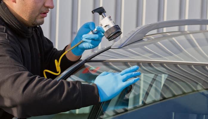 Technician repairing crack in upper part of windshield