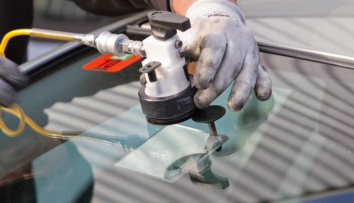 Mechanic repairing crack in car windshield