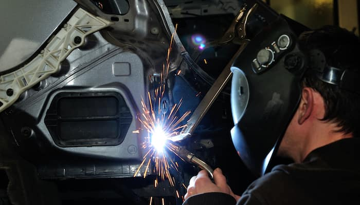Mechanic with face mask welding two car panels together