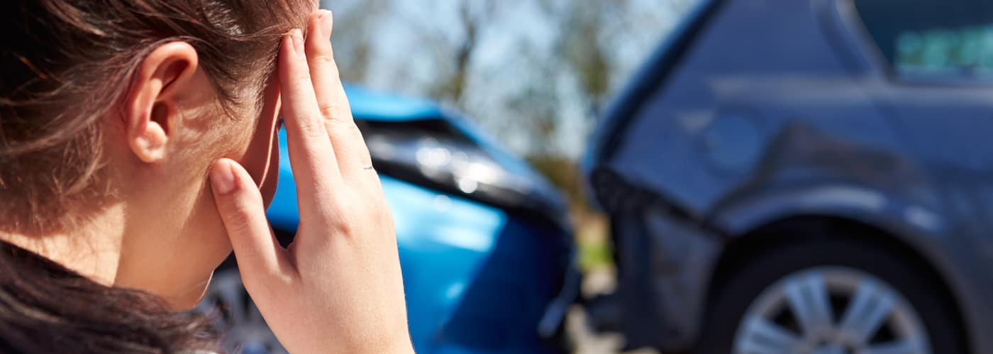 Stressed woman looking at damage from car collision