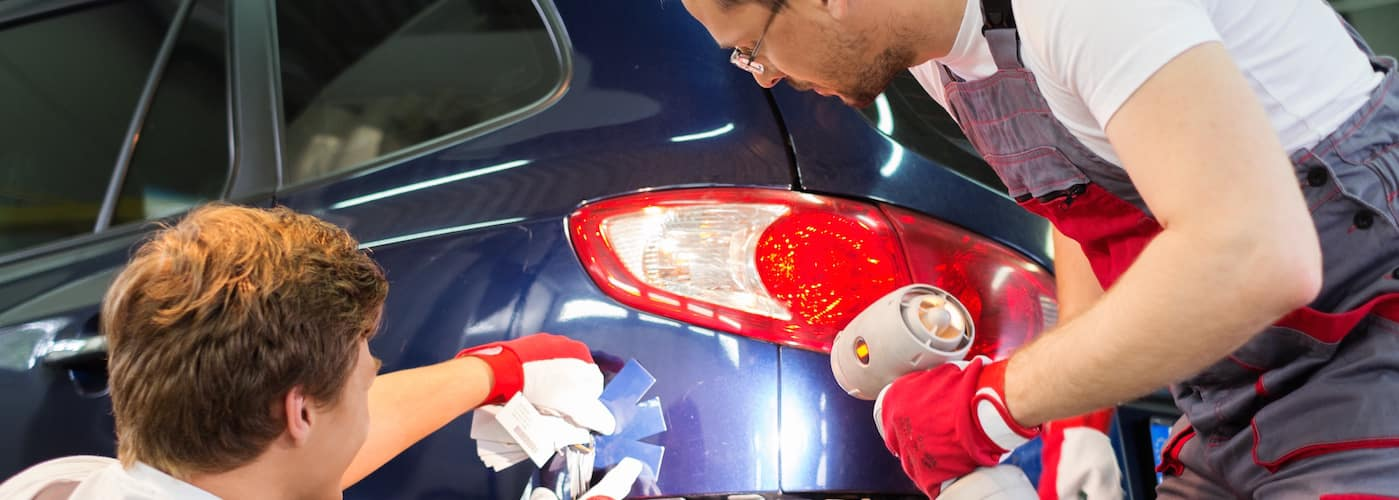 Two technicians applying paint to vehicle