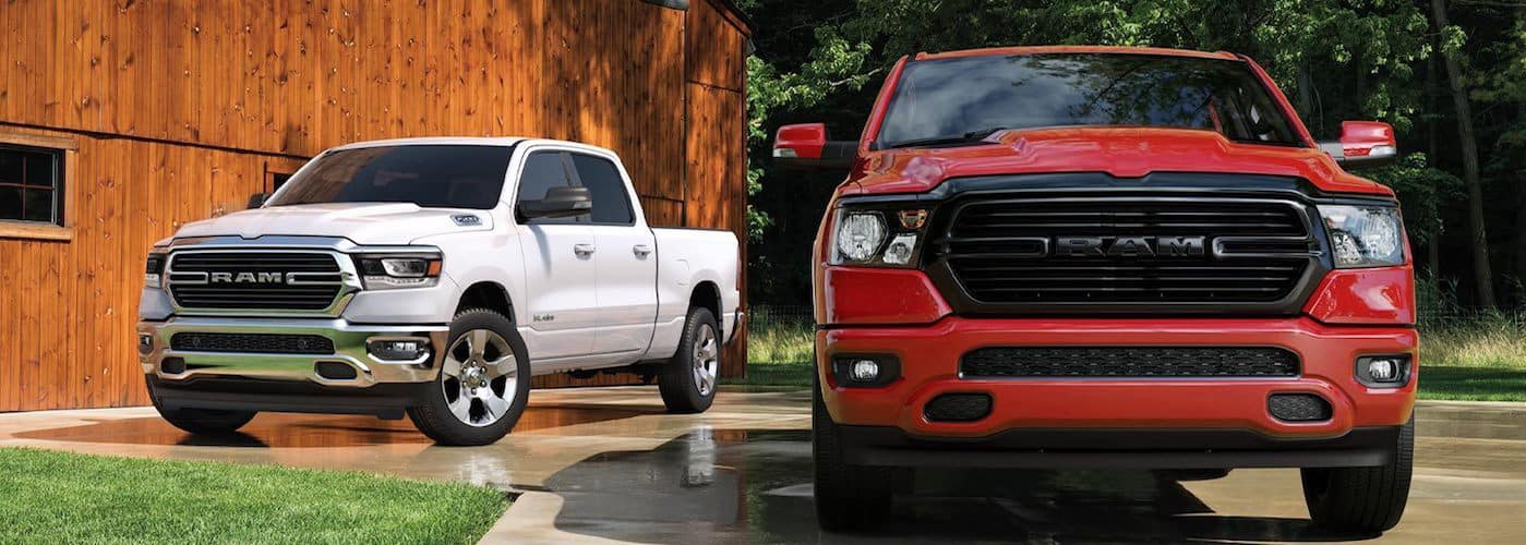 White RAM 1500 and red RAM 1500 parked near a barn