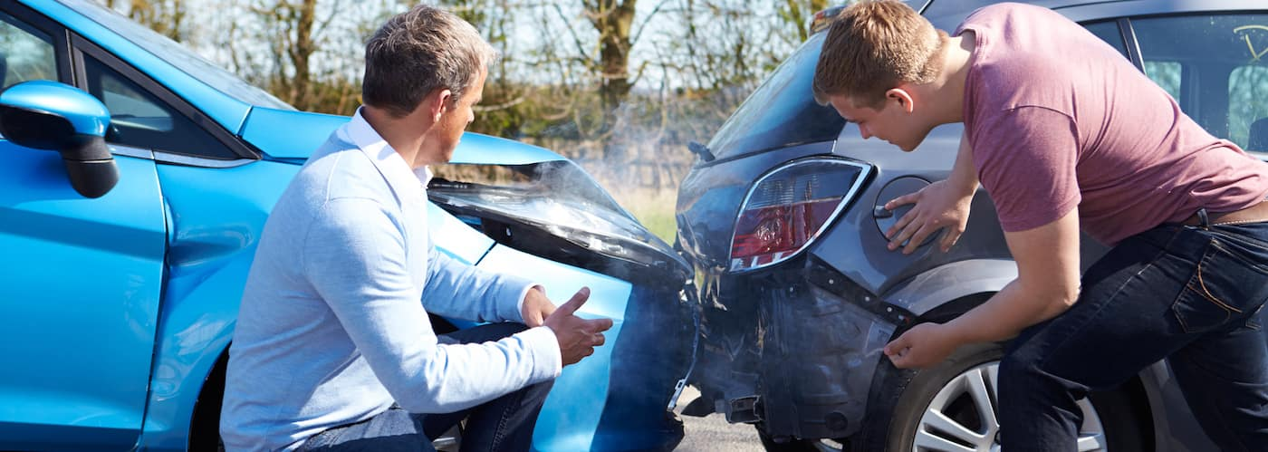 Drivers inspecting car accident damage