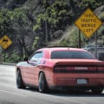 a red dodge challenger driving away with a mountainous background