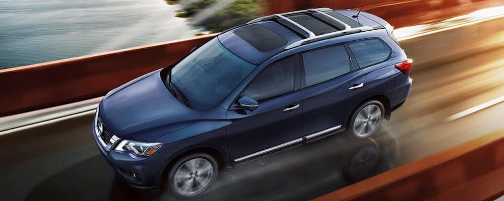 Blue 2018 Nissan Pathfinder driving across bridge with blurred background