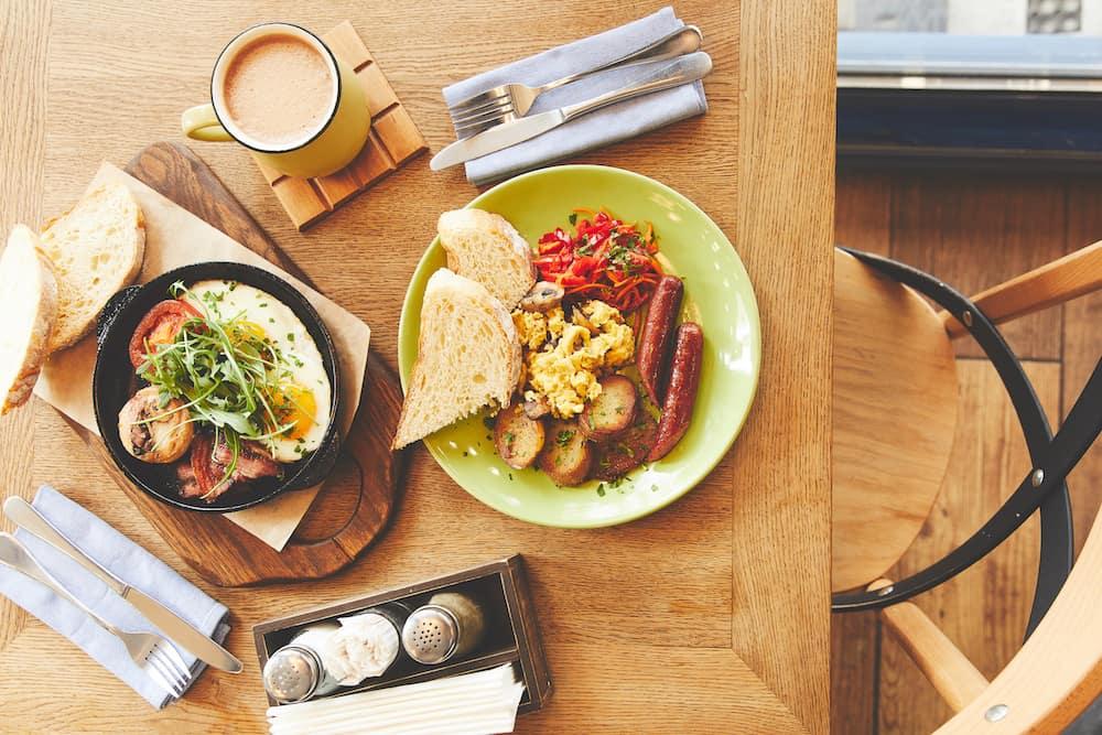 Savory breakfast skillet, sausage, coffee on wood table
