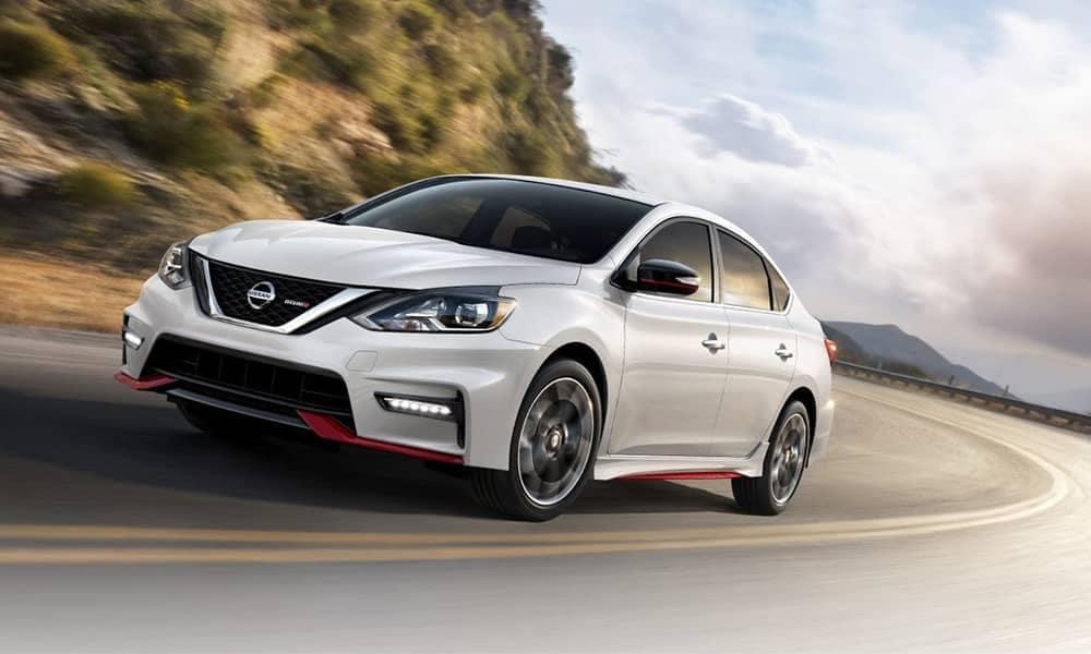 White 2019 Nissan Sentra driving around corner