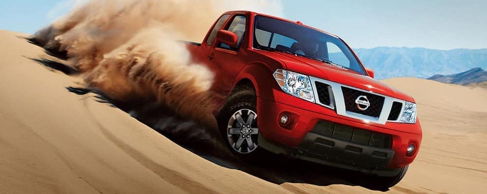 Red 2019 Nissan Frontier driving through desert with clouds of sand behind it