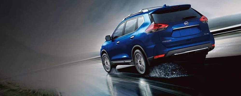 2019 Nissan Rogue speeding down a wet track