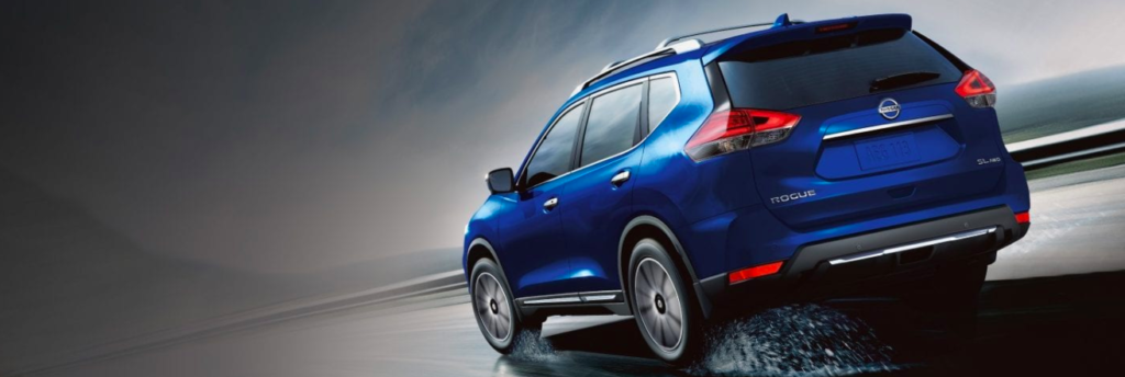 Blue 2019 Nissan Rogue driving on a wet road