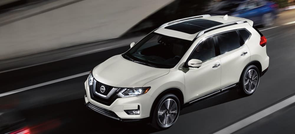 Exterior view of a 2020 Nissan Rogue driving on a city street at night