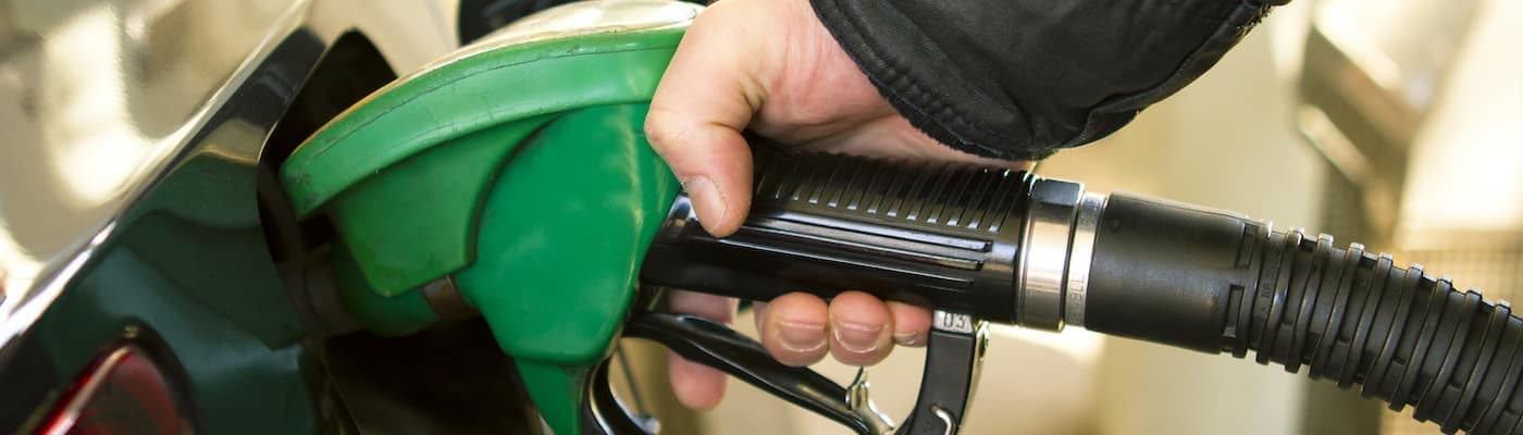 A man filling up a car with premium gas