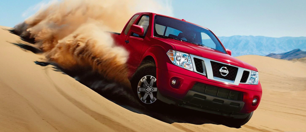 A Nissan Frontier driving through sand dunes