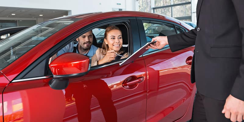 Couple signing papers on new car