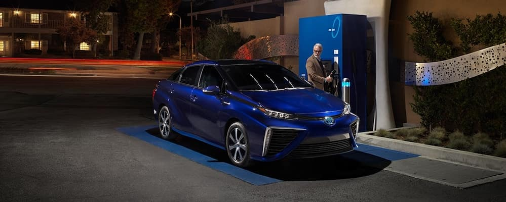 Man Filling Up Blue Toyota Mirai at Night
