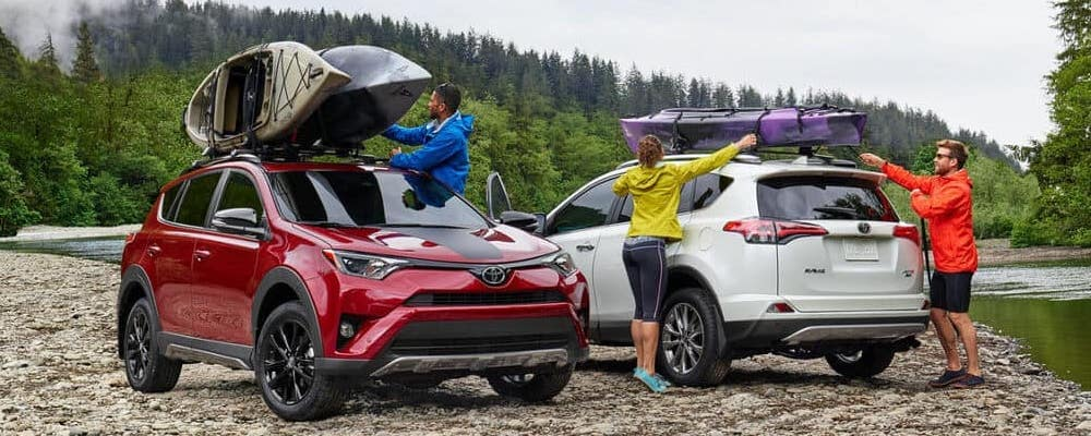 People placing boats on Red Toyota RAV4 Adventure AWD and White Toyota RAV4 Platinum AWD in woods