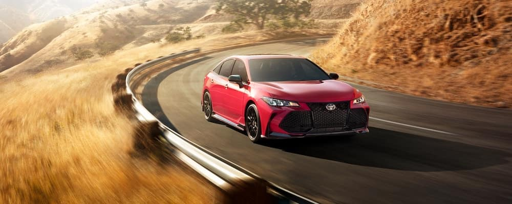 2020 Toyota Avalon TRD moving around a curve on a sunny day.