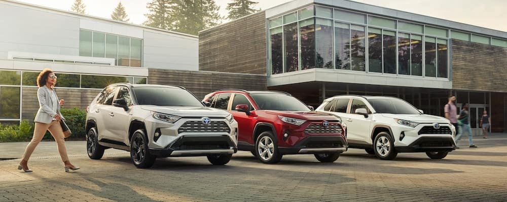 Silver, red, and white Toyota RAV4 crossovers in front of building at sunrise, women walking in front of them