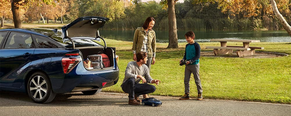 Family of three enjoying outdoors at a park with 2019 Toyota Mirai carrying their outdoor gear