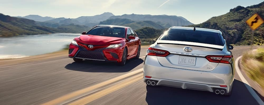 White 2019 Toyota Camry driving away while red 2019 Toyota Camry drives toward the camera. Two 2019 Toyota Camry models passing each other on mountain highway.