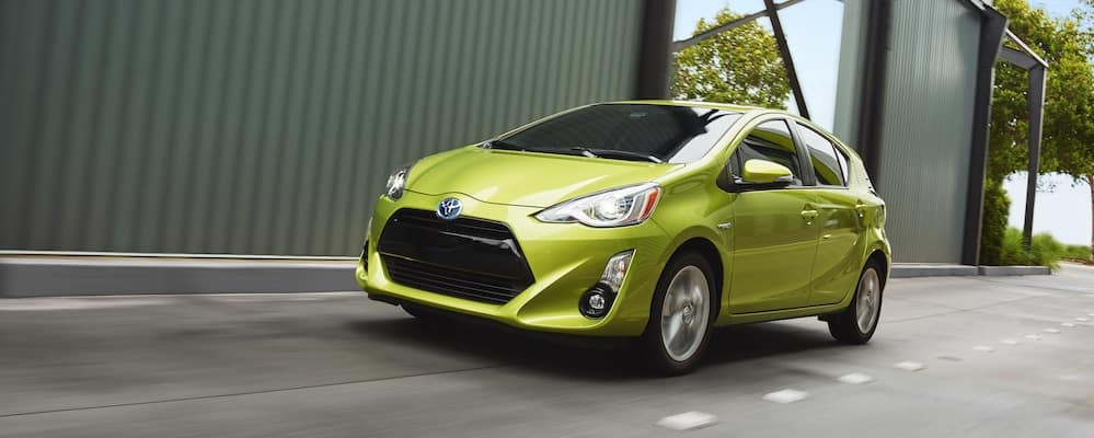 Lime green Toyota Prius c driving on city street