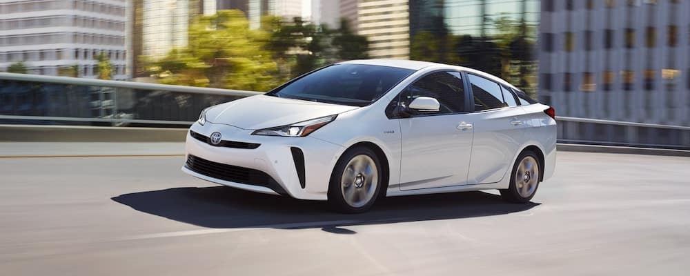 White 2019 Toyota Prius on city highway with blurred city background
