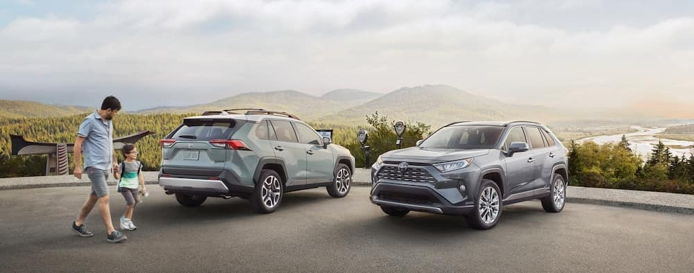 Father and daughter walking up to two 2019 Toyota RAV4 models overlooking mountains