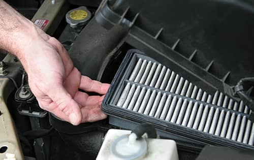 mechanic replacing air filter