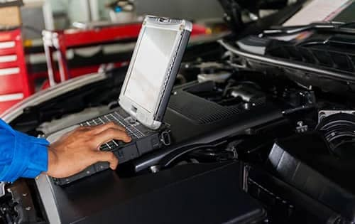 mechanic with computer in car engine