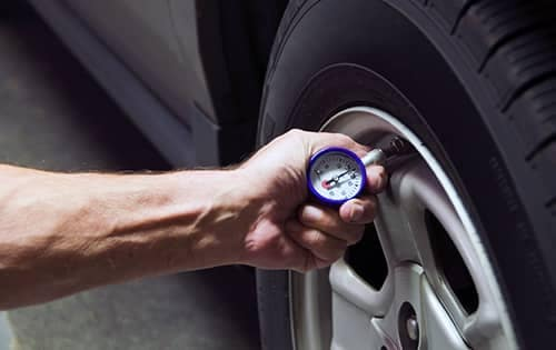 Mechanic checking tire pressure