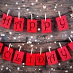 Red Tags with Happy Holidays on it Hanging on a Line on Wood with Snow, Christmas or Winter Holiday Greetings