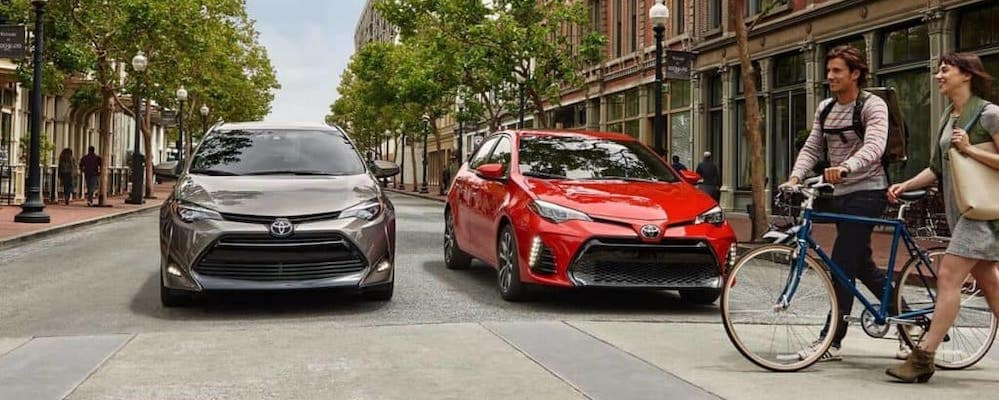 Two Toyota Corollas wait for people to cross street