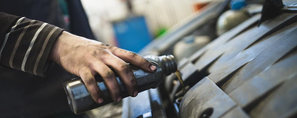 Unseen mechanic pouring motor oil into car engine