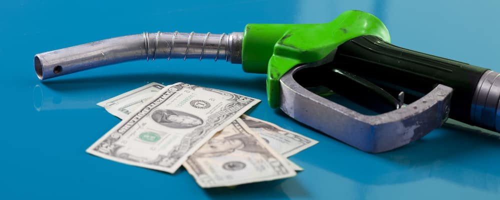 Green fuel pump with money next to it against blue background