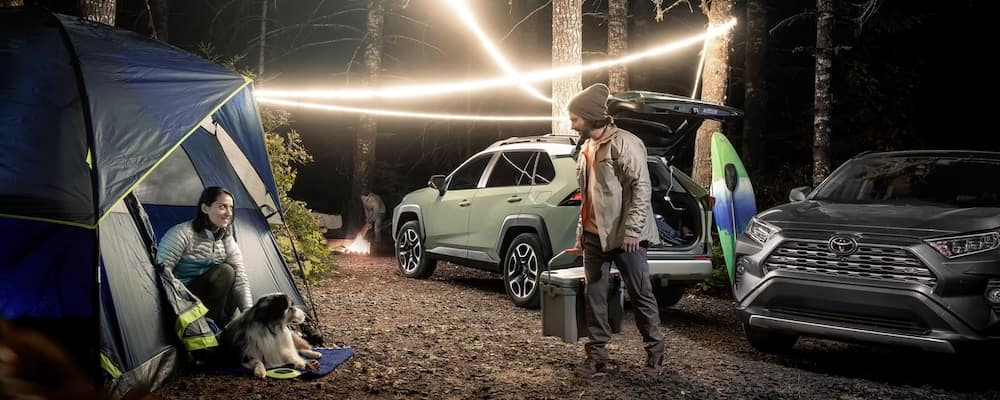 People using 2019 Toyota RAV4 for camping at night with strung up lights in woods.