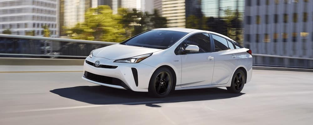 White 2020 Toyota Prius Limited driving on city street