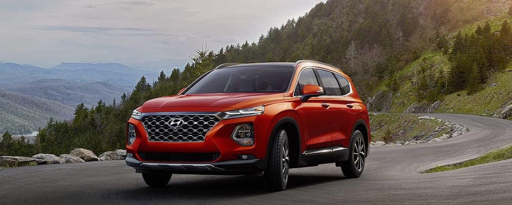Lava Orange 2019 Hyundai Santa Fe driving on mountain road