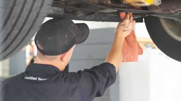 Service technician wipes down car