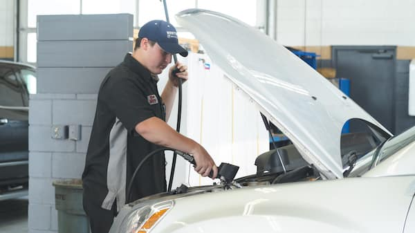 A service technician working on a car